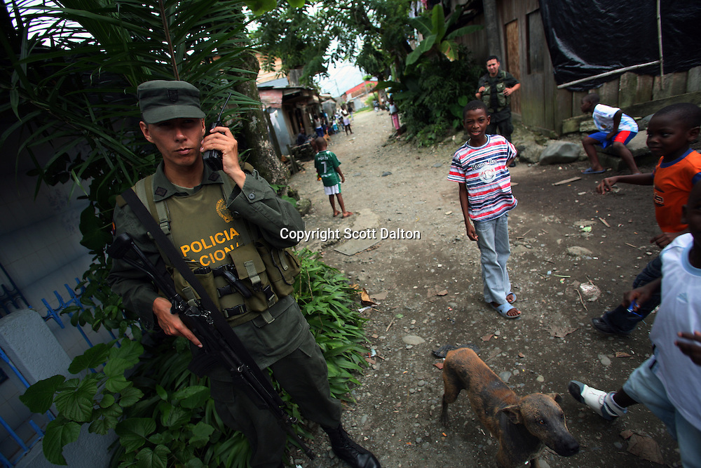 A police officer keeps guard on the street of Lleras, a poor barrio in Buenaventura, on the Pacific Coast of Colombia, on Sunday, May 13, 2007. Buenaventura is in the midst of a spree of violence over control of drug shipments from the poor barrios in the city. Many of the neighborhoods have a strong presence of FARC militias that control most of the drug trade in the city. (Photo/Scott Dalton)