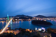 Dolsan Deagyo suspension bridge at Yeosu is lit with changing color lights after sunset.