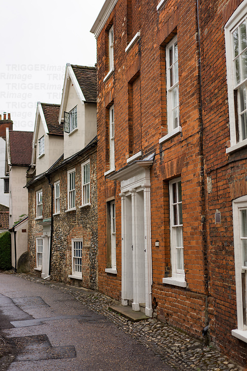 Old narrow street in Norwich England with brick and flint housing