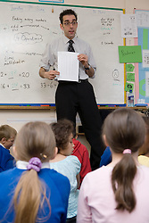Teacher standing in front of whiteboard talking to group of school children,
