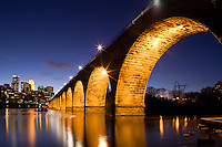 The famous Stone Arch Bridge at dusk with reflections in the Mississippi river in Minneapolis, Minnesota.