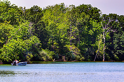 28 May 2015:   A fisherman plies his trade from a small watercraft or boat with an outboard motor at Comlara Park and Evergreen Lake in the northwest region of McLean County Illinois<br /> <br /> <br /> This image was produced in part utilizing High Dynamic Range (HDR) processes.  It should not be used editorially without being listed as an illustration or with a disclaimer.  It may or may not be an accurate representation of the scene as originally photographed and the finished image is the creation of the photographer.