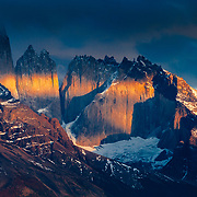 The first rays of sunlight bathe the Towers of Paine in light through an opening in the storm clouds in Torres del Paine National Park, Chile.