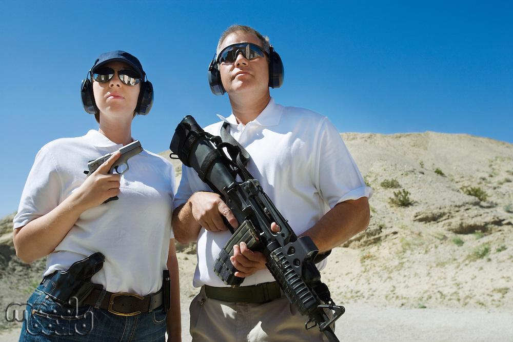 Man and woman holding guns at firing range in desert
