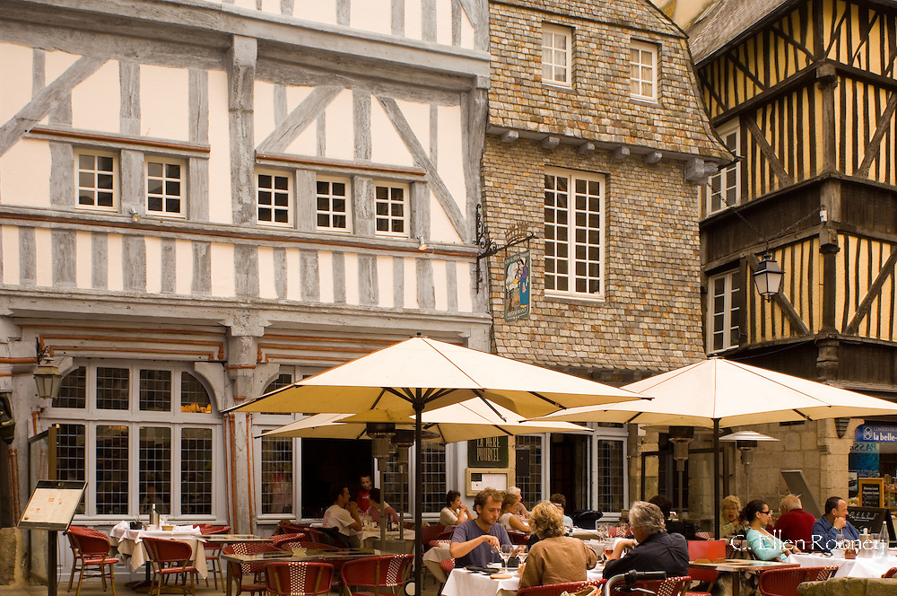 A cafe next to the medieval half timbered buildings in Dinan, Brittany, France