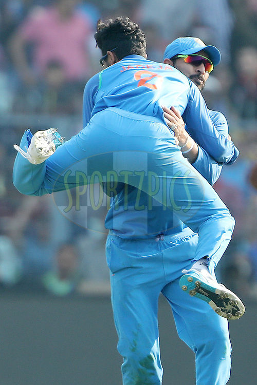 Ravindra Jadeja of India celebrates the wicket of Jason Roy of England with Yuvraj Singh of India  during the third One Day International (ODI) between India and England  held at Eden Gardens in Kolkata on the 22nd January 2017<br /> <br /> Photo by: Ron Gaunt/ BCCI/ SPORTZPICS