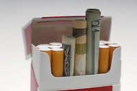 Money rolled up in cigarette box, close-up