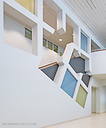 Modern office multistory lobby. White with color insets as art, installed to be an architectural centerpiece