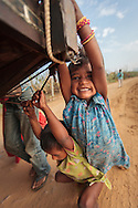 Young gypsy children holding on to the back of a camel cart at the Pushkar Camel Fair, Rajasthan, India