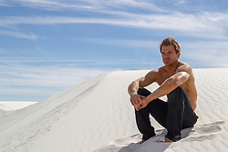 sexy man in White Sands, NM sitting on a sand dune