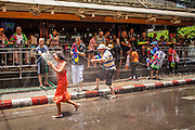 13 APRIL 2013 - BANGKOK, THAILAND:    Foreign tourists throw water on a Thai woman during a Songkran water fight on Soi Nana, off of Sukhumvit Road in Bangkok. Songkran is celebrated in Thailand as the traditional New Year's Day from 13 to 16 April. The date of the festival was originally set by astrological calculation, but it is now fixed. If the days fall on a weekend, the missed days are taken on the weekdays immediately following. Songkran is in the hottest time of the year in Thailand, at the end of the dry season and provides an excuse for people to cool off in friendly water fights that take place throughout the country. Songkran has been a national holiday since 1940, when Thailand moved the first day of the year to January 1. PHOTO BY JACK KURTZ