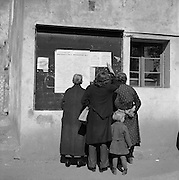 Germans in an occupied town reading instructions from Americans on a bulletin board.