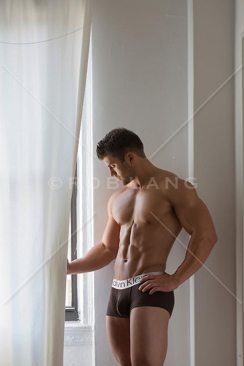 bodybuilder standing by a window in his underwear