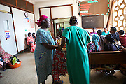 Sister Sulphine Twinomuhangi (in green) helps ladies whist they wait at Mulago Hospital, Uganda.