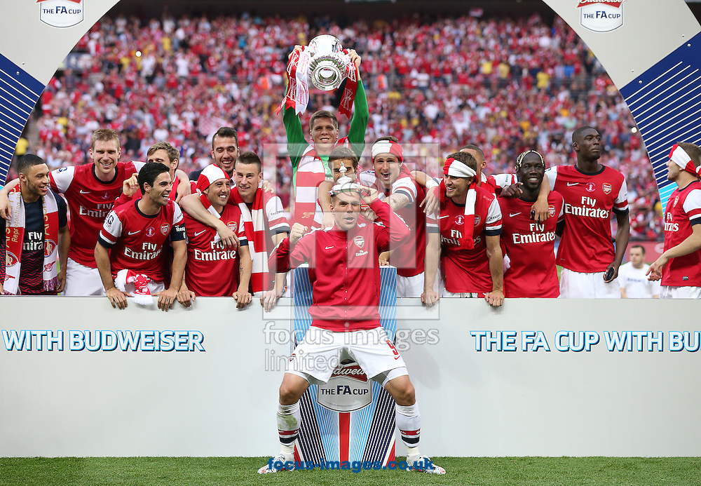 Lukas Podolski ( C ) celebrates with the rest of the Arsenal team after they win the The FA Cup Final match at Wembley Stadium, London<br /> Picture by Paul Terry/Focus Images Ltd +44 7545 642257<br /> 17/05/2014