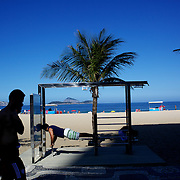A man works out at a fitness station at the edge of Ipanema beach, Rio de Janeiro,  Brazil. 4th July 2010. Photo Tim Clayton....