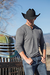 cowboy leaning against an old truck