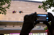 An audience member snaps a photo as BANDALOOP performs on the exterior of the Memorial Union during the Madison World Music Festival on September 12, 2014.