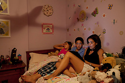 "Vanessa Gonzalez gets her children, Andrea and Santiago, ready for bed with a bedtime story, Littleton, Colo., Aug. 29, 2011. Santiago, 13, is a full-time college student at the Colorado School of Mines, an engineering university. He wakes up at 5:30 a.m. every morning during the academic semester to develop iPad and iPhone applications in a programming language called Objective C, which he learned from a textbook when he was 9 years old. That textbook and 86 similar volumes including Applied Finite Mathematics, Infinity in Your Pocket, Programming in C++ and Dictionary of Physics, sit in a glass-fronted bookcase opposite his bed. ""Exceptionally gifted"" is the commonly used phrase for kids as smart as Gonzalez."