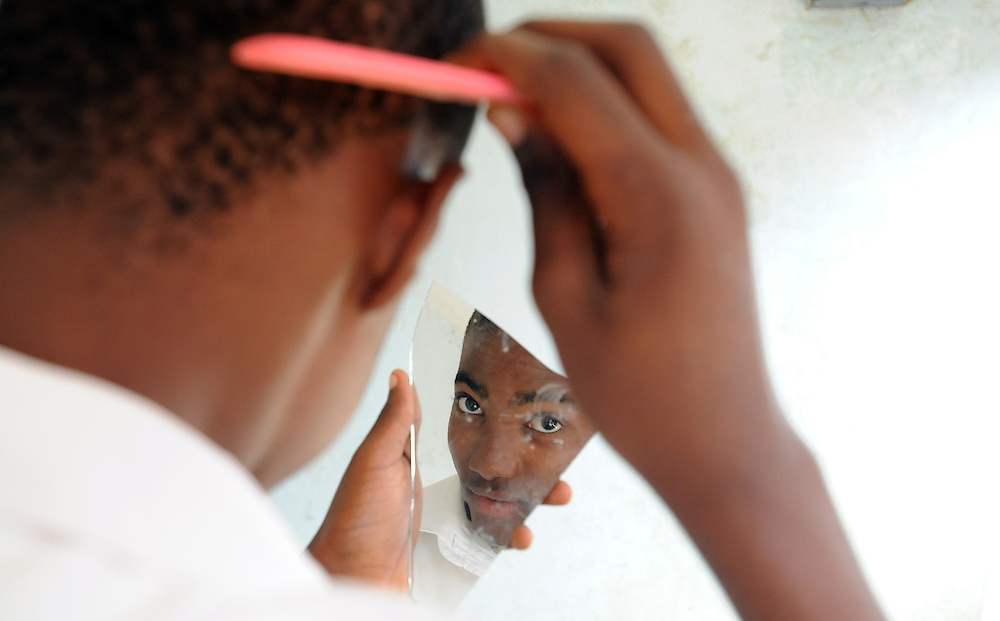 Nacir Mangus (16) prepares himself for school at his home in Maputo, Mozambique. Nacir is the head of his household since his parents died from AIDS related illness and he looks after his three siblings.