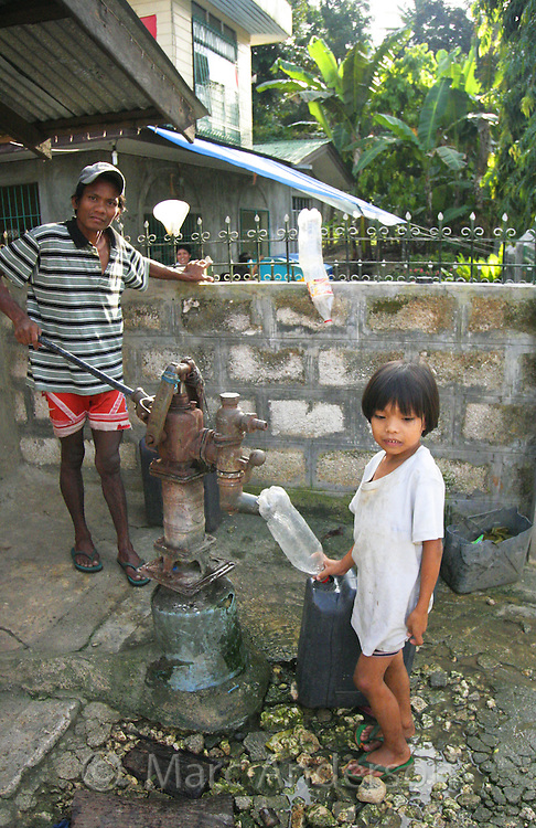 A young girl collecting water in a bottle at a well, as her father pumps the water in the background, Bohol, Philippines.