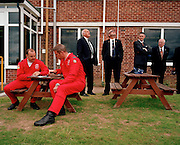 With great concentration, Flight Lieutenant Dan Simmons and Squadron Leader David Thomas of the elite 'Red Arrows', Britain's Royal Air Force aerobatic team, meticulously brief themselves for their forthcoming air display at the RAF College at Cranwell, Lincolnshire. The two pilots, dressed in their famous red flying suits, stand out from a small group of Ministry of Defence (MoD) drivers who stand around with time to spare, some looking skyward at other overhead aerobatics. The 'Synchro Pair' (Reds 6 and 7) are the two pilots whose aircraft make the most dynamic of the manoeuvres including a cross called the Opposition Barrel Roll where both pilots aim at each other at closing speeds of 760 mph.Since 1965 the Red Arrows have flown over 4,000 such shows in 52 countries.