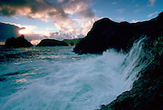 Waves breaking against the cliffs making sea spray at Kinance Cove, Cornwall, England, United Kingdom