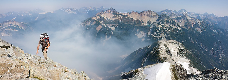 Jim Prager scrambles up Whatcom Peak in North Cascades National Park, Washington. Smoke from a nearby forest fire gathers in the valley below.