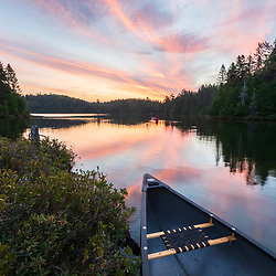 A woman paddles a canoe in Island Pond in Aroostook County, Maine. Deboullie Public Reserve Land.