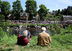 © Licensed to London News Pictures. <br /> 06/06/2014. <br /> <br /> Appleby, Cumbria, England<br /> <br /> Two men look on as horses are taken into the River Eden to be washed as is the tradition as gypsies and travellers gather during the annual horse fair on 6 June, 2014 in Appleby, Cumbria. The event remains one of the largest and oldest events in Europe and gives the opportunity for travelling communities to meet friends, celebrate their music, folklore and to buy and sell horses.<br /> <br /> The event has existed under the protection of a charter granted by King James II in 1685 and it remains the most important event in the gypsy and traveller calendar.<br /> <br /> Photo credit : Ian Forsyth/LNP