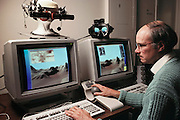 Virtual reality: Lewis Hitchner manipulates a pair of video images of the Valles Marineris of the planet Mars, computer-generated from data provided by the Viking spacecraft at NASA's Ames Research Centre, California. Sophisticated computers & sensors provide the user with a telepresence in the virtual world, through small video screens mounted in goggles on a headset, whilst a spherical joystick controls movement through the virtual landscape. One future Martian application of this system might be in gathering geological samples by remote control using a rover robot. A sensor in the geologist's headset could direct the robot at specific sample targets. Model Released (1990)