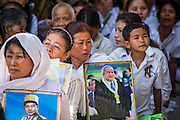 """04 FEBRUARY 2013 - PHNOM PENH, CAMBODIA:  Cambodians sit in the shade near the National Museum with photos of former Cambodian King Norodom Sihanouk during his cremation service in Phnom Penh. Norodom Sihanouk (31 October 1922- 15 October 2012) was the King of Cambodia from 1941 to 1955 and again from 1993 to 2004. He was the effective ruler of Cambodia from 1953 to 1970. After his second abdication in 2004, he was given the honorific of """"The King-Father of Cambodia."""" Sihanouk died in Beijing, China, where he was receiving medical care, on Oct. 15, 2012.   PHOTO BY JACK KURTZ"""