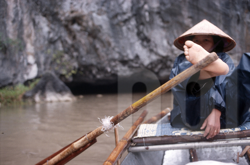 Color film photograph of a Vietnamese woman guiding her small boat with a bare foot, Tam Coc, Ninh Binh, Vietnam, Southeast Asia
