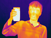 A Thermogram of a boy witha hot glass of water.  This image is part of a series.  The different colors represent different temperatures on the object. The lightest colors are the hottest temperatures, while the darker colors represent a cooler temperature.  Thermography uses special cameras that can detect light in the far-infrared range of the electromagnetic spectrum (900?14,000 nanometers or 0.9?14 µm) and creates an  image of the objects temperature..