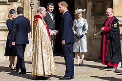 Windsor, UK. 21st April 2019. The Duke of Sussex shakes the hand of the Dean of Windsor, the Rt Revd David Conner KCVO, as he arrives to attend the Easter Sunday service at St George's Chapel in Windsor Castle. Princess Anne, Princess Royal, looks on.