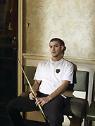 Young man sitting on chair holding a billiards stick.