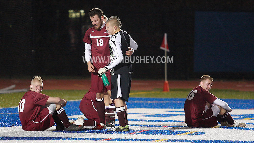 Fort Ann goalie Jonah Gould hugs Derek Durkee (18) after Chazy scored in the second overtime periold to defeat Fort Ann 2-1 in the Class D state semifinals at Faller Field in Middletown on Saturday, Nov. 16, 2013.