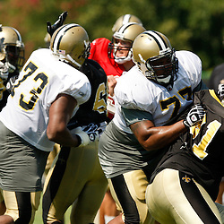 July 31, 2010; Metairie, LA, USA; New Orleans Saints guard Carl Nicks (77) blocks defensive end Will Smith (91) during a training camp practice at the New Orleans Saints practice facility. Mandatory Credit: Derick E. Hingle
