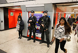 © Licensed to London News Pictures. 27/04/2017. London, UK. Extra armed police officers watch over commuters at Green Park Tube station in London, shortly after aman was arrested carrying what is reported to be a bag full of knives, on Whitehall in Westminster, central London. Photo credit: Tolga Akmen/LNP