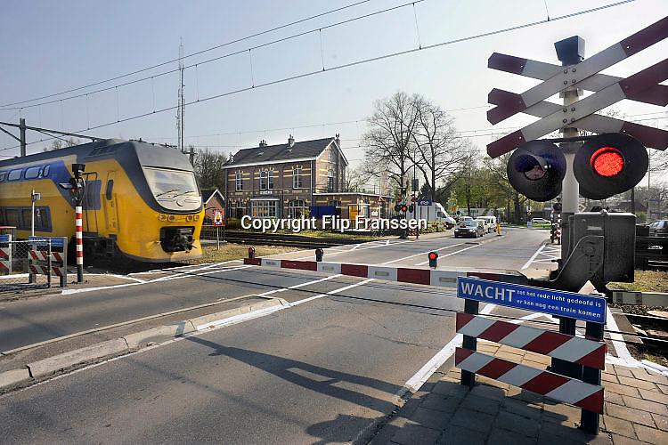 Nederland, Wolfheze, 15-4-2016Trein passeert de spoorwegovergang met halve slagbomen bij het station van Wolfheze.Foto: Flip Franssen