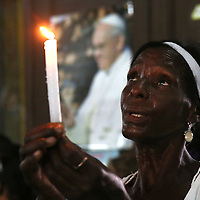 (092415  Havana, Cuba) With a photo of Pope Francis behind her, a woman holds up a candle and prays on the Feast of Our Lady of Mercy inside Our Lady of Mercy Church in Old Havana, Thursday,  September 24, 2015. photo by Angela Rowlings.