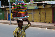 A man carrying a large bundle of material on his head on the street in Dhaka, Bangladesh.