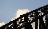 Tourists climb on the top of the Sydney Harbour Bridge in the late afternoon as part of the Sydney Harbour Bridge Climb which operates dusk to dawn seven days a week.