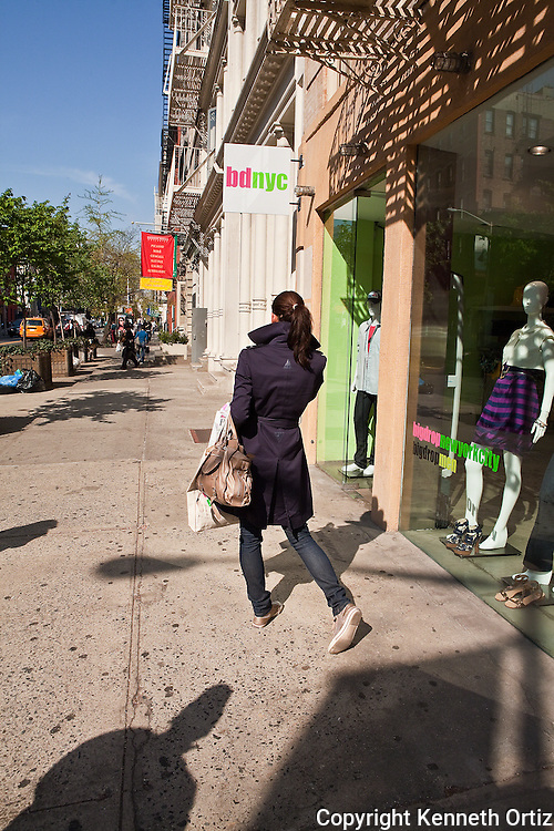 A woman on West Broadway in the West Village in New York City talks on her cell phone as she looks north towards Houston Street.