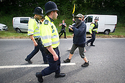 © London News Pictures. 27/07/2013. Balcombe, UK.  An activist confronting police as they escort a lorry on to the site. Anti Fracking activists and local villagers attempt to blockade a drilling site in Balcombe, West Sussex which has been earmarked for fracking. A number of demonstrators at the site have been arrested. Photo credit: Ben Cawthra/LNP
