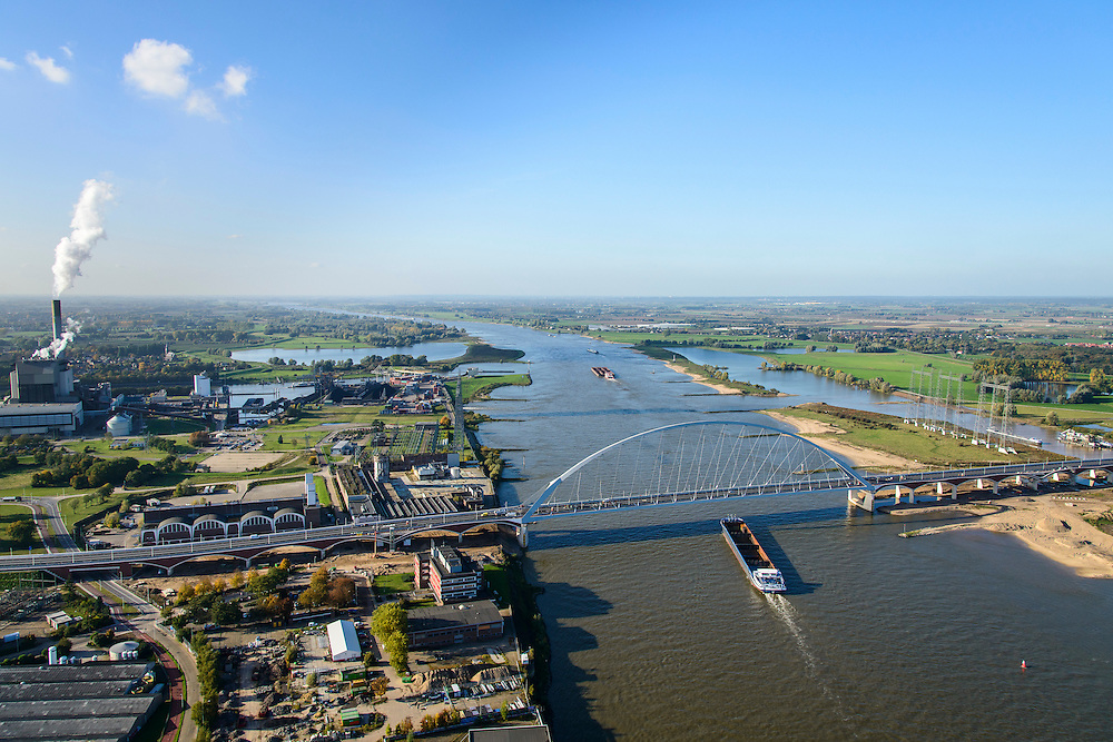 Nederland, Gelderland, Nijmegen, 24-10-2013; de nieuwe stadsbrug van Nijmegen over rivier de Waal, De Oversteek. Rechts van de rivier grondwerkzaamheden voor de Dijkteruglegging Lent (Ruimte voor de Rivier). Links industrie- en havengebied met de monding van het Maas-Waalkanaal.<br /> The new city bridge of Nijmegen on the river Waal, De Oversteek (The Crossing). On the right groundworks for the Dike relocation of Lent (project Ruimte voor de Rivier: Room for the River). <br /> luchtfoto (toeslag op standaard tarieven);<br /> aerial photo (additional fee required);<br /> copyright foto/photo Siebe Swart.
