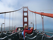 A tourist takes a photograph while riding across the Golden Gate Bridge atop a double decker tour bus on June 16, 2008 in San Francisco, California. (Photo by Kevin Bartram)
