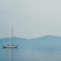 Sail boat moored on calm lake with distend headland