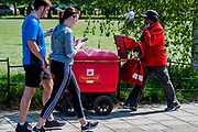 A couple are so engrossed on their phones that they give no social distance to the postwoman as she makes a mail delivery across the Common - Clapham Common is reasonably busy as the sun is out and it is warmer. The 'lockdown' continues for the Coronavirus (Covid 19) outbreak in London.