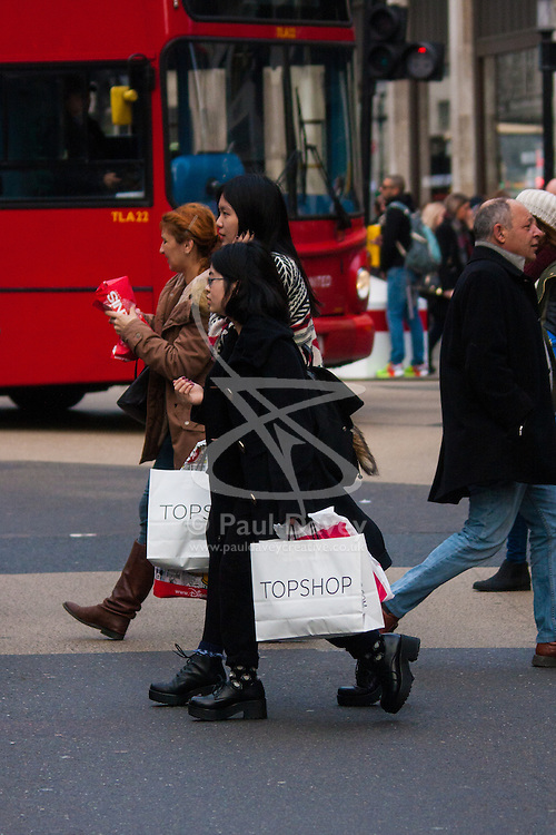 """London, December 23rd 2014. Dubbed by retailers as the """"Golden Hour"""" thousands of shoppers use their lunch hour to do some last minute Christmas shopping in London's West End. PICTURED: Shoppers with their fistfuls of bags at Oxford Circus."""